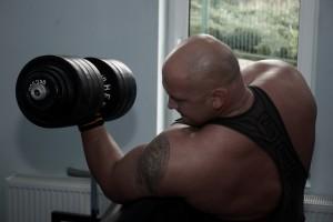 Kamil Bazelak podczas treningu bicepsów z 45kg sztangielką